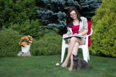 Woman in the yard reading book Stock Photography