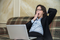 Woman yawing on sofa Stock Image