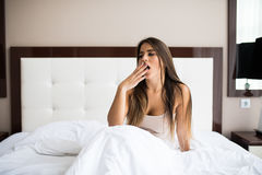 Woman yawning in bed at home. Sleepy young woman yawning in bed at home Stock Images