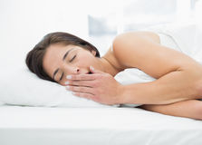 Woman yawning in bed. Young woman yawning in bed with eyes closed stock images
