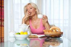 Woman yawning at breakfast table Stock Photography