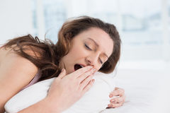 Woman yawning with eyes closed in bed Royalty Free Stock Photography