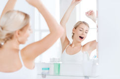 Woman yawning in front of mirror at bathroom Stock Image