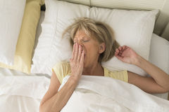 Woman Yawning While Lying In Bed Royalty Free Stock Photos