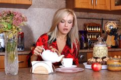 Woman with yeapot and cup of hot drink Royalty Free Stock Photos