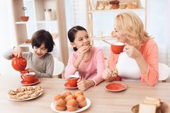 Woman in years with cheerful grandson and granddaughter eating cookies and drinking tea in red mugs at kitchen. Beautiful grandmother with her grandchildren at Stock Photos