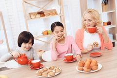 Woman in years with cheerful grandson and granddaughter eating cookies and drinking tea in red mugs at kitchen. Beautiful grandmother with her grandchildren at Stock Image