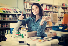 Woman 20-24 years old is purchasing tools for house improvements. In paint supplies store Royalty Free Stock Image