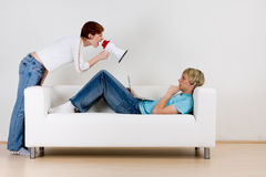 Woman yelling into bullhorn. Young woman yelling into bullhorn at young man laying on couch Stock Images