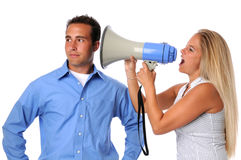 Woman Yelling at Man. Young woman using megaphone to communicate to uninterested man