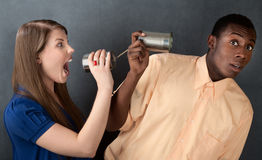 Woman Yelling at Man Through Stringed Cans. Woman shouts at a man through stringed cans on gray background Stock Image