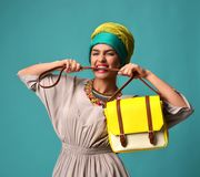 Woman yelling screaming and eating belt of hand hold stylish fashion yellow leather bag handba. G isolated on blue mint background Royalty Free Stock Images