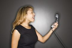 Woman yelling into telephone. Royalty Free Stock Images