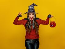 Woman on yellow background with jack-o-lantern frightening. Colorful halloween. modern woman in halloween witch costume on yellow background with jack-o-lantern stock images