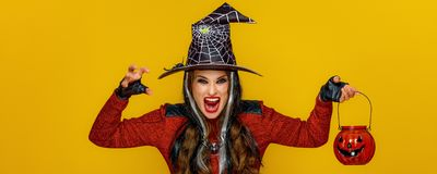 Woman on yellow background with jack-o-lantern frightening. Colorful halloween. modern woman in halloween witch costume on yellow background with jack-o-lantern royalty free stock photos
