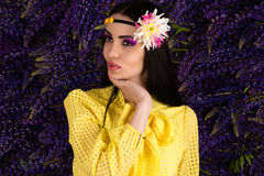 Woman in yellow on background lupine flowers Stock Photo