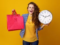 Woman on yellow background showing clock and red shopping bags. Smiling trendy woman with long wavy brunette hair on yellow background showing clock and red royalty free stock photography