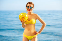 Woman with yellow ball in the sea Stock Images