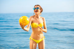 Woman with yellow ball in the sea Stock Photos