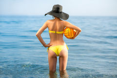 Woman with yellow ball in the sea Royalty Free Stock Photography