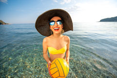 Woman with yellow ball in the sea Royalty Free Stock Photos