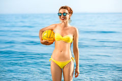 Woman with yellow ball in the sea Royalty Free Stock Photo