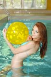 Woman with yellow beach ball having fun Stock Images