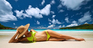 Woman in yellow bikini lying on beach at Seychelles Stock Images