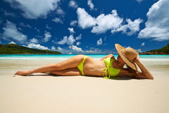 Woman in yellow bikini lying on beach at Seychelles Stock Photo