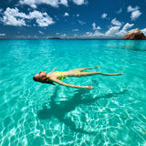 Woman in yellow bikini lying on water Royalty Free Stock Image