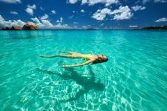 Woman in yellow bikini lying on water Royalty Free Stock Photo