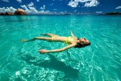 Woman in yellow bikini lying on water Stock Images