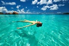 Woman in yellow bikini lying on water Stock Photos