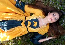 Woman in Yellow and Blue Dress Lying on a Grass Field Stock Photo