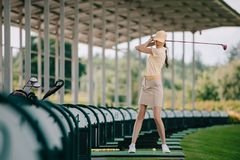 woman in yellow cap and polo playing golf
