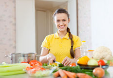 Woman in yellow chopping cucumber Stock Photo