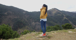 Woman in yellow coat near mountain valley Royalty Free Stock Photo