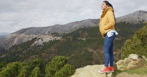 Woman in yellow coat near mountain valley Royalty Free Stock Image