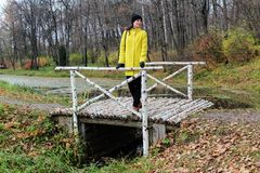 A woman in a yellow coat is standing on a birch bridge in the estate of Count Leo Tolstoy in Yasnaya Polyana.  Stock Photos