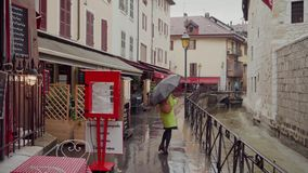 Woman in yellow coat walk by old european streets in rainy weather with black polka-dot umbrella. 4k stock video footage
