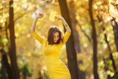 Woman in the yellow dress with autumn leaves in hand and fall yellow maple garden background Royalty Free Stock Photography