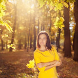 Woman in the yellow dress with autumn leaves in hand and fall yellow maple garden background Stock Image