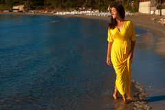 Woman with yellow dress on a  beach. Royalty Free Stock Photography