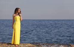 Woman in yellow dress on the beach Stock Images