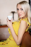 Woman in a yellow dress behind a table in cafe Stock Image