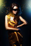 Woman in yellow dress and black mask Stock Photography