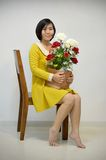 Woman in yellow dress with a bouquet of roses Royalty Free Stock Photo