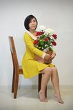 Woman in yellow dress with a bouquet of roses Stock Image