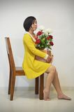 Woman in yellow dress with a bouquet of roses Stock Images