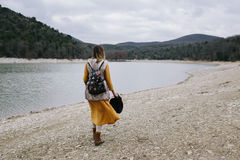 Woman in a yellow dress and with floral backpack walks along the lake shore royalty free stock images